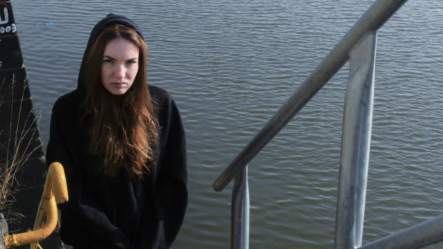 Young-Serious-Faced-Woman-Standing-on-River-Staircase