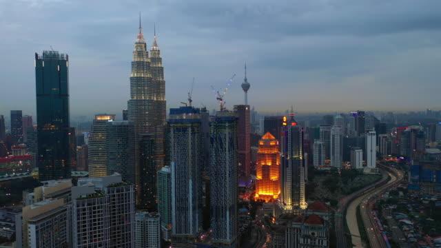 Crepúsculo-iluminación-kuala-lumpur-centro-de-la-ciudad-camino-del-tráfico-aéreo-Malasia-panorama-4k