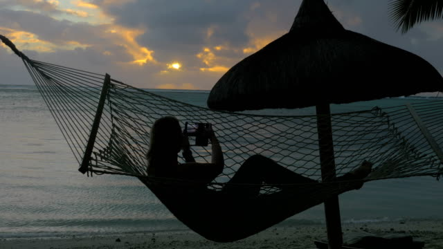 Woman-relaxing-in-hammock-on-beach-and-taking-cell-photos