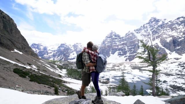 Junges-Paar-in-den-kanadischen-Rockies-Wandern-erreichen-Berggipfel-und-feiern-mit-einer-Umarmung