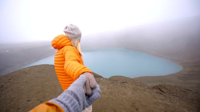 Follow-me-to-the-crater-lake-girlfriend-leading-man-to-volcanic-crater-in-Iceland-People-travel-concept-4K-video
