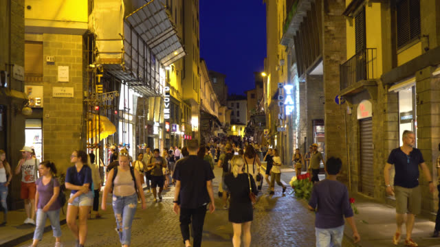 Florence-Tuscany-Italy-People-walk-along-the-illuminated-Via-Via-Por-Santa-Maria-at-night