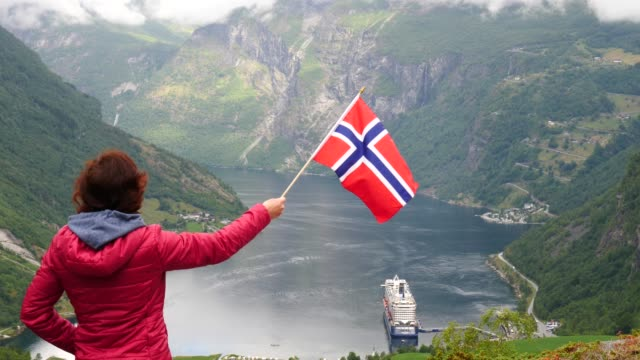 Tourist-with-norwegian-flag-and-cruise-ship-on-fjord