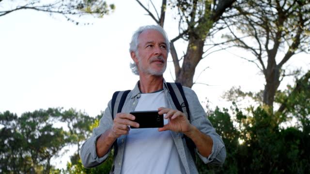 Senior-hombre-clic-en-fotos-con-el-teléfono-móvil-en-el-campo-4k