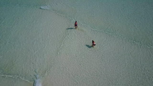 v03806-Aerial-flying-drone-view-of-Maldives-white-sandy-beach-on-sunny-tropical-paradise-island-with-aqua-blue-sky-sea-water-ocean-4k-2-people-young-couple-man-woman-playing-ball-fun-together