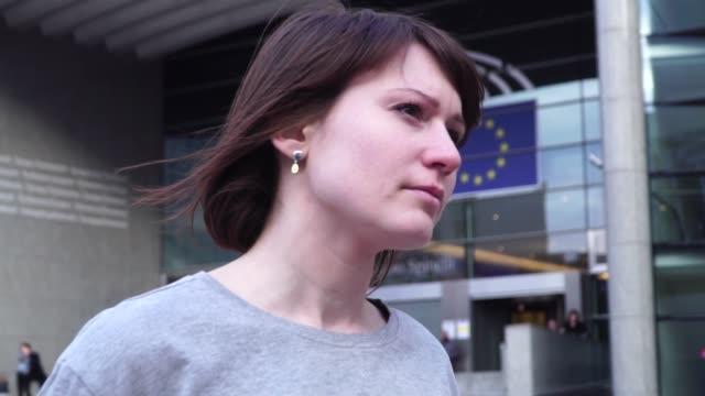 Señora-turista-camina-y-mira-a-lugares-de-interés-cerca-del-Parlamento-Europeo-en-Bruselas-Bélgica-efecto-de-zoom-lento-motion-dolly