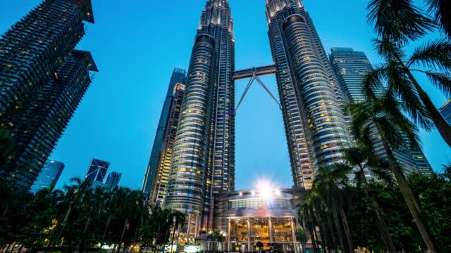 Timelapse-de-Close-up-tiro-las-Torres-Petronas-de-Kuala-Lumpur-en-sunset-4K-Incline-hacia-arriba-