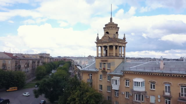 Drone-flight-near-the-old-style-tower-with-factory-on-the-background