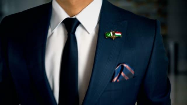 Empresario-caminando-hacia-cámara-con-amigo-país-banderas-Pin-Pakistán---Hungría