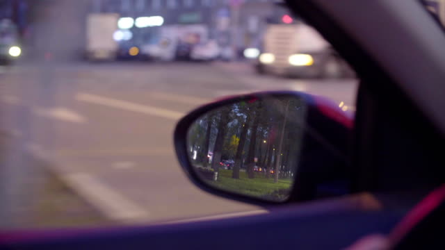 View-of-the-city-traffic-in-car-s-rearview-mirror