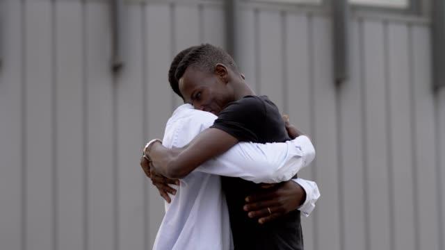 Familienfoto:-zwei-schwarze-afrikanische-Brüder-umarmen-in-der-Straße