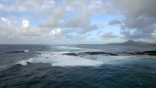 Aerial-view-of-water-line-of-seas-that-do-not-mix-against-blue-sky-with-clouds-Mauritius-Island