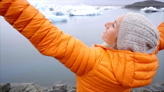 Cámara-lenta-chica-estirados-brazos-en-Laguna-de-glaciar-en-Islandia