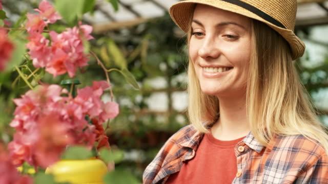 Mujer-alegre-cuidando-para-planta-de-flor-floreciente