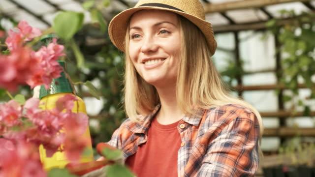 Mujer-feliz-cuidando-flores-en-invernadero
