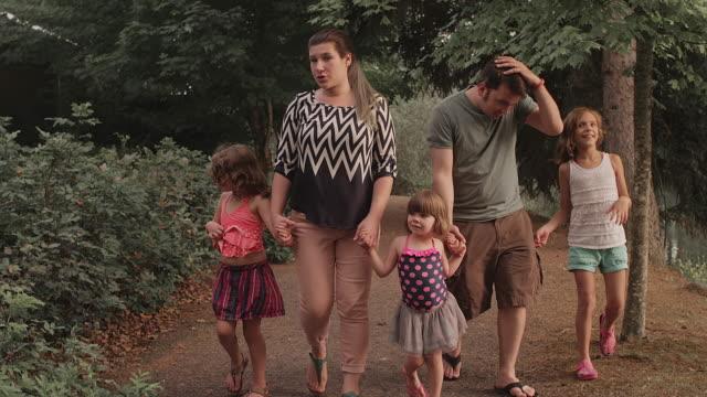 Una-familia-caminando-por-un-sendero-en-el-parque-Mientras-sostiene-manos