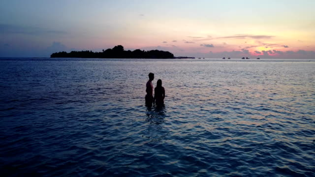 v04157-Aerial-flying-drone-view-of-Maldives-white-sandy-beach-2-people-young-couple-man-woman-romantic-love-sunset-sunrise-on-sunny-tropical-paradise-island-with-aqua-blue-sky-sea-water-ocean-4k