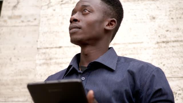Retrato-de-hombre-afroamericano-atractivo-usando-tableta-digital-al-aire-libre