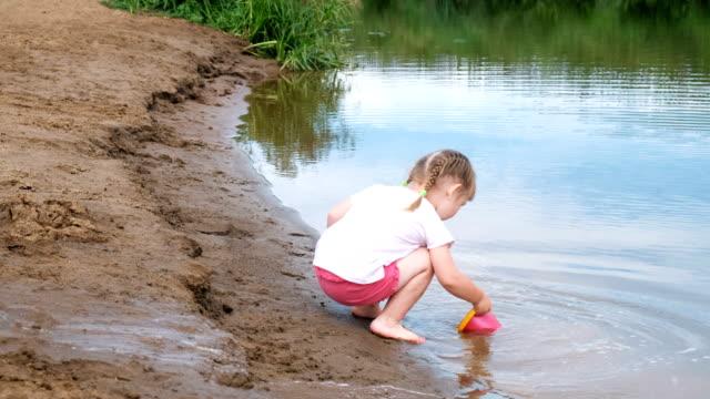Kleine-Mädchen-holt-und-gießt-Wasser-aus-dem-Eimer-in-den-Sand-Kinder-spielen-am-Strand