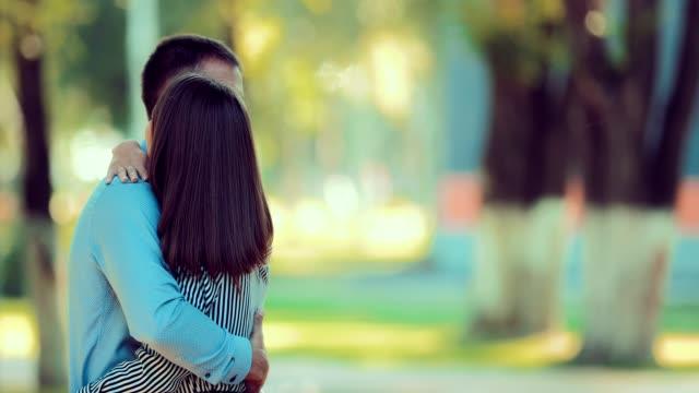 Mädchen-und-Freund-umarmt-im-Park-bei-Sonnenuntergang