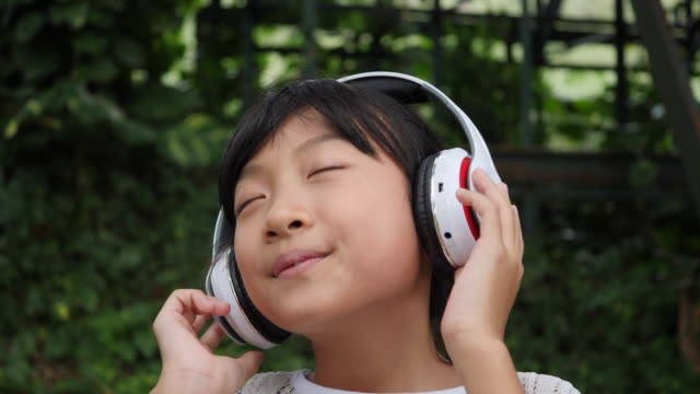 Little-girl-listens-to-music-from-headphone-and-good-feeling