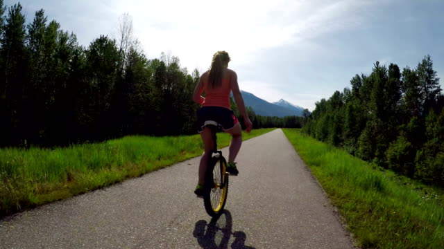 Mujer-montando-monociclo-en-la-carretera-4k