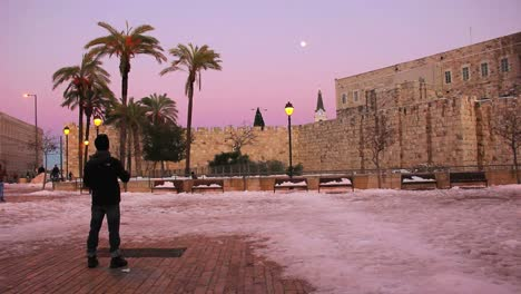 A-man-stands-in-a-square-in-Jerusalem-at-dusk-following-a-rare-snow-fall