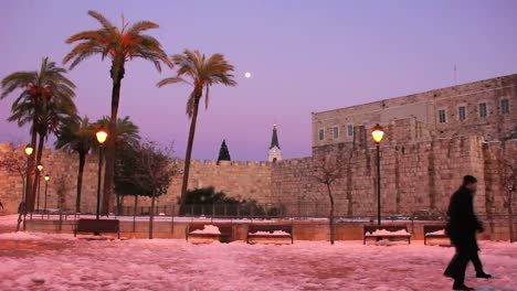 People-pass-through-a-square-in-Jerusalem-at-dusk-following-a-rare-snow-fall