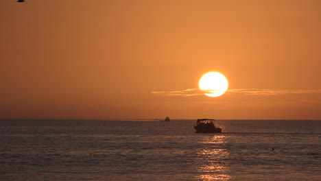 A-motorboat-passes-on-the-ocean-at-sunset