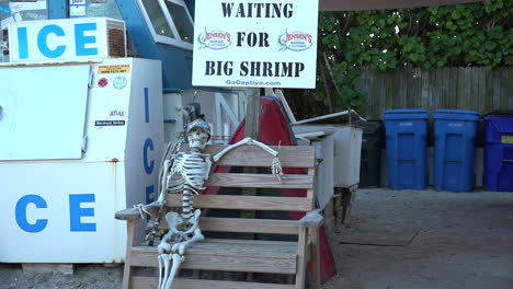 A-humorous-display-shows-a-skeleton-waiting-for-big-shrimp