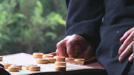 Old-folks-play-mah-jong-or-chinese-checkers-in-a-park-in-China-as-passersby-watch