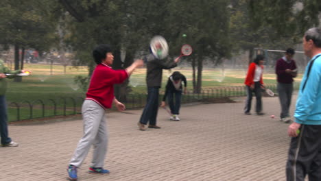 People-in-a-park-in-China-play-an-exercise-game-with-a-ball-and-paddle-