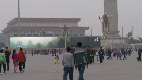 Chinese-troops-march-through-Tiananmen-Square-with-large-electronic-billboard-background