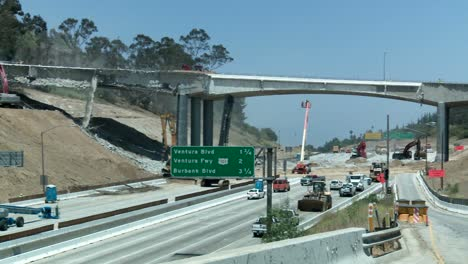 Wide-view-of-heavy-equipment-tearing-down-part-of-a-bridge-over-the-405-freeway-in-Los-Angles