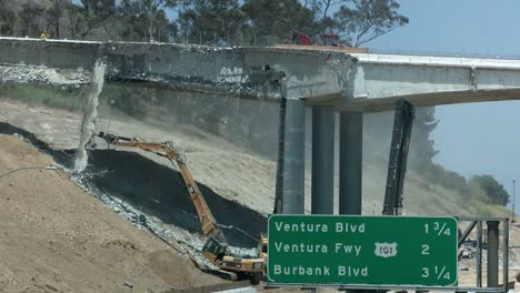Construction-crews-tear-down-a-portion-of-a-bridge-stretching-over-the-405-freeway-in-Los-Angeles