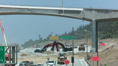 Excavators-dig-near-an-empty-stretch-of-the-405-freeway-in-Los-Angles-as-crews-tear-down-part-of-a-bridge