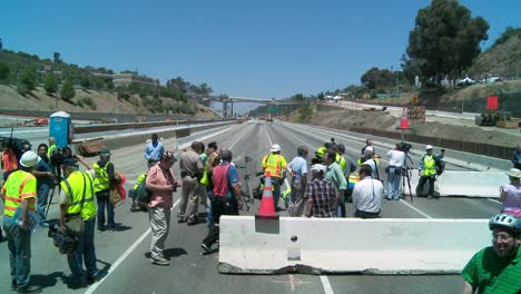 Zoom-out-from-crews-working-on-a-closed-of-the-405-freeway-in-Los-Angles-to-show-a-crowd-of-onlookers