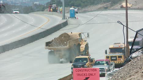 Dump-trucks-haul-earth-away-from-an-empty-stretch-of-the-405-freeway-in-Los-Angles-as-crews-tear-down-part-of-a-bridge