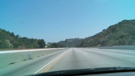 Car-driving-down-an-empty-stretch-of-freeway-in-Los-Angeles-with-construction-vehicles-visible-in-the-closed-down-lanes-at-left