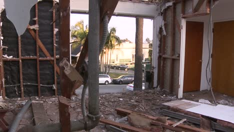 Cars-pass-on-the-street-outside-a-home-in-the-process-of-being-demolished
