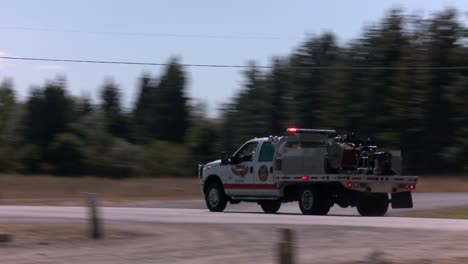 Emergency-personnel-race-down-a-highway-in-a-rural-area