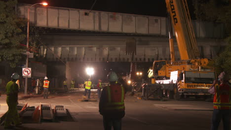 Construction-workers-work-on-a-freeway-overpass-at-night-in-Los-Angeles