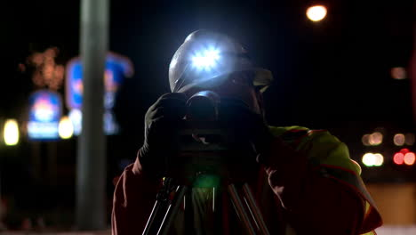 An-American-surveyor-works-at-night-on-a-road-construction-project
