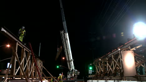 Construction-workers-work-on-a-freeway-overpass-at-night-in-Los-Angeles-3