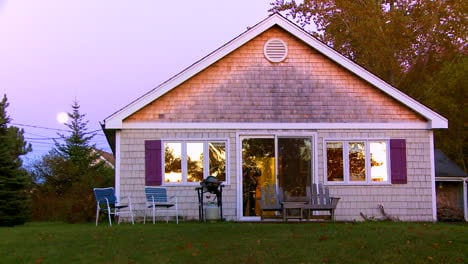 Nice-dusk-establishing-shot-of-a-summer-cottage-in-New-England-or-Maine-with-moon-rising