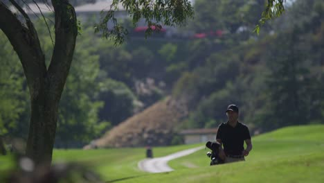 A-golfer-carries-his-clubs-as-a-walks-up-a-hill-on-a-golf-course