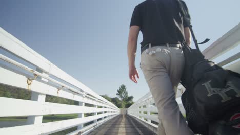 A-golfer-walks-up-a-walkway-away-from-the-camera-as-the-camera-pulls-back
