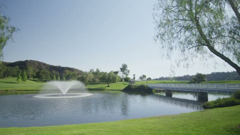 Pan-left-wide-view-of-a-golf-course-with-a-fountain-lake-and-bridge