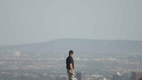 Wide-tilt-down-view-of-a-golfer-walking-on-a-golf-course-with-mountains-and-a-city-in-the-background