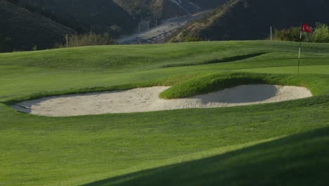 Wide-view-of-a-sand-trap-at-a-golf-course-with-mountains-in-the-background